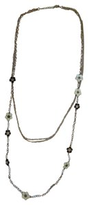 Other Three chain goldtone necklace with flower of black and ivory color with little pearls.