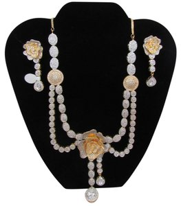 Rose style necklace with white stones in gold and white tone metal.