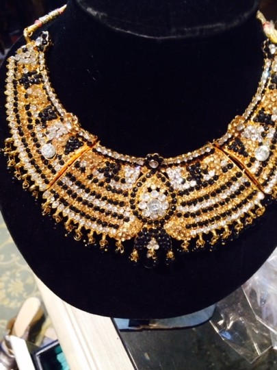 Other elaborate collar with beautiful stones set in a metal base..gold,black,amber & clear inset jewels