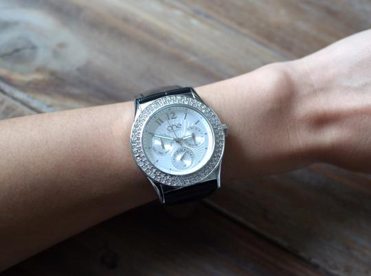 One watch company by the one One watch company by the one black white genuine leather bracelet watch featured with rhinestone swalovski details.