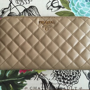 Prada Tan Prada quilted long wallet with gold-tone logo plate at front, eight card slots, bill folds, interior zip pocket and zip around closure.