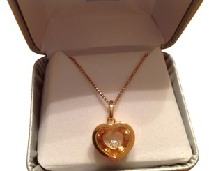 Chopard Chopard rose gold necklace with floating diamond in center of pendant.