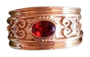 Gold scroll ring with garnet stone and diamond acents