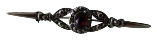 Shiekh vintage broach with a maroon stone in the middle.