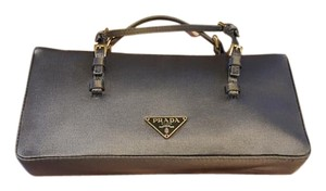 Prada The color is called aluminum. It's a gray color with gold hardware. Clutch