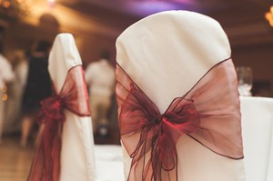 Ivory Chair Covers And Burgundy Sashes