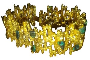 golden tone bracelet with green stones