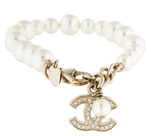 Chanel Gold-tone Chanel interlocking CC faux pearl charm bracelet