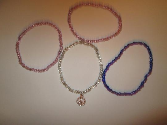 Other 4 bracletts / 2 pink/ 1 blue/ 1 clear with peace sign charm. Costume Image 1
