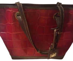 Dooney & Bourke Tote in Crimson Red, brown handles, gold tone hardware accessories.