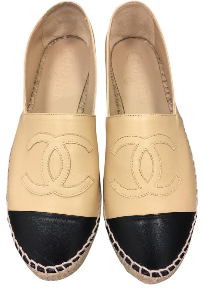 Quilted nappa leather flats in beige with black patent cap toe. Handmade in Spain. Handmade in Spain, these flats offer more than a sense of ease and sophistication. The insole is fully padded for maximum comfort and there is an adjustable band around the top of the shoe for a customized fit.