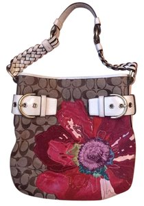 Coach Satchel in Brown canvas with multicolor flower. White leather handle and accents.