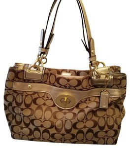 Coach Satchel in brown logo Coach purse with gold metallic trim. gently used, very well taken care of. a few pen ink marks on insides from normal wear and use.