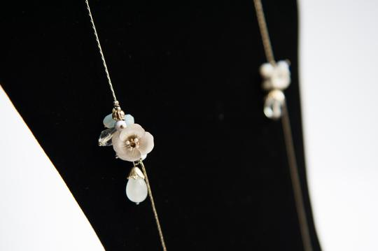 Anthropologie long gold tone with white and pink flowers