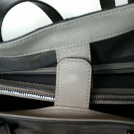 Vince Camuto Tote in Gray leather with outside black and white calfskin pocket, with toggle closure.