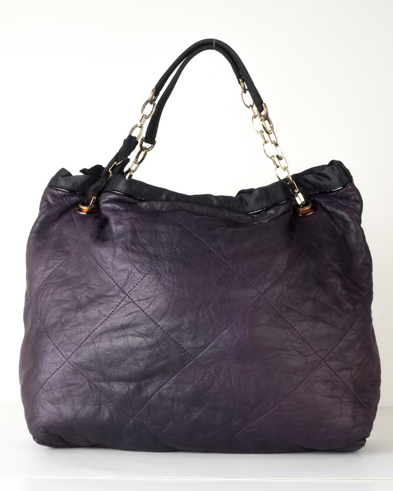 Lanvin tote bag printed blue, purple, black fabric with black satin cotton canvas lining and two pockets, one zipped. Worn by hand or on shoulder. On the handle there is the famous.