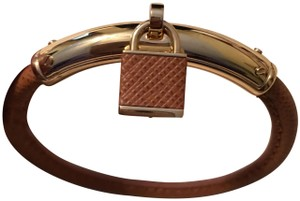 Michael Kors Brown leather and gold tone padlock bracelet by Michael Kors.