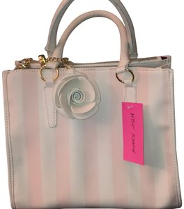 Betsey Johnson Satchel in white and pink stripe outside on front/back. sides of exterior are white with stitching. inside is lined in purple with hot pink lips and other Betsy Johnson type design.