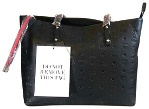 MCM Tote in Black with red contrast underneath handles and red zipper pull.