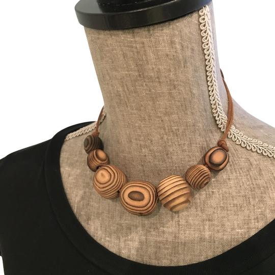 Preload https://img-static.tradesy.com/item/24597731/ivory-brown-adjustable-etched-wood-chokernecklace-with-double-leather-tie-necklace-0-1-540-540.jpg