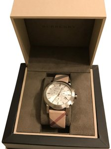 Burberry This beautiful Burberry BU9357 Women's Analog watch features a white/ivory dial with a check leather strap