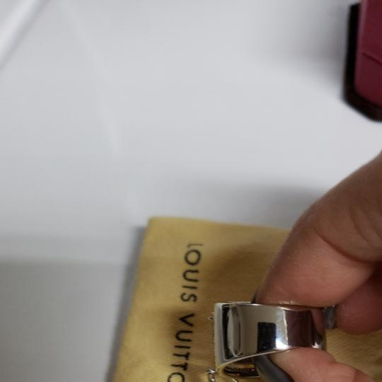 Louis Vuitton Louis Vuitton silver and gold tone ring size 9.5 with silver and gold tone signature LV charms adorning. Minor scratches not noticable when wearing. Worm a couple of times, but it is too large for me to wear comfortably. Purchased from another seller that was mistaken on the size.
