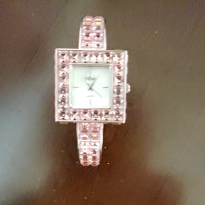quartz Beautiful pink Swarovski crystal watch with mother of pearl face. Quartz time piece runs, but needs a new battery. I purchased this piece in Las Vegas at the Liberace museum. Minor scratches from minimal wear.