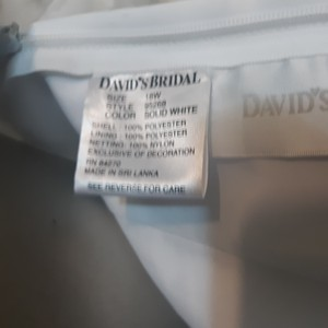 David's Bridal Solid White Shell Polyester. Lining Polyester. Netting Nylon. 95268 Formal Wedding Dress Size 18 (XL, Plus 0x)