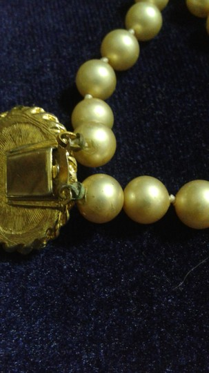 Other Vintage Pearl neckage with a stone that is turquoise color with gold veins.