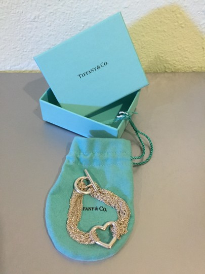 Tiffany & Co. Sterling silver by Tiffany & Co multi strand roll chain mesh heart bracelet. Toggle closure with open heart center. Length 6 inches. Piece comes with original box and pouch. Like new, worn 2 to 3 times.