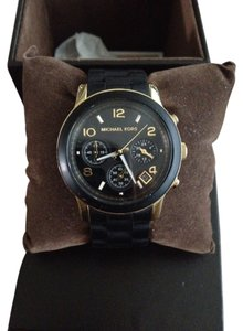 Michael Kors Gold tone stainless steel case with fixed black rubber bezel.