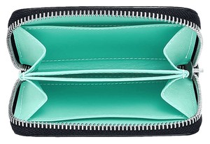 Tiffany & Co. Wallet in grain leather with palladium-plated solid brass hardware. Tiffany Blue leather lining with two main gusset compartments, one center slip pocket and two slip pockets. Zipper closure and Tiffany & Co. logo plaque with Tiffany Blue stitch detail. 4.25