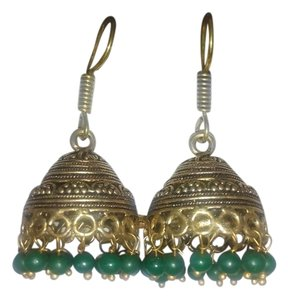 gold and black metal earrings (jhumkas) with green tassels.